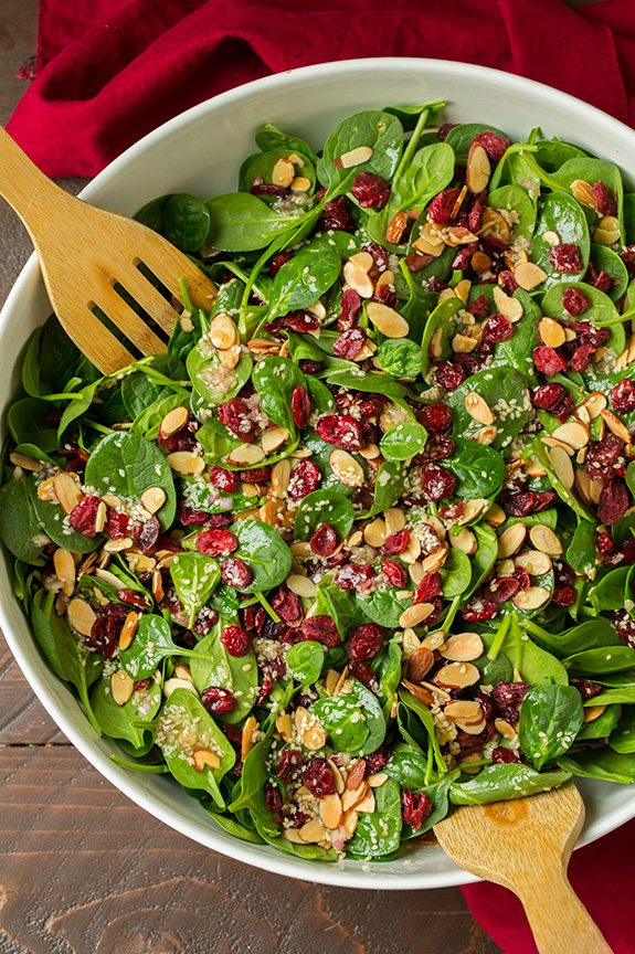 Overhead image of spinach salad in a large salad bowl with wooden serving spoons.