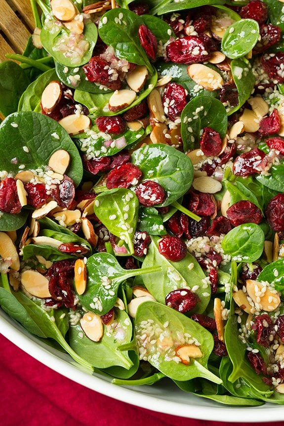 Close up image of spinach salad in a white salad bowl.