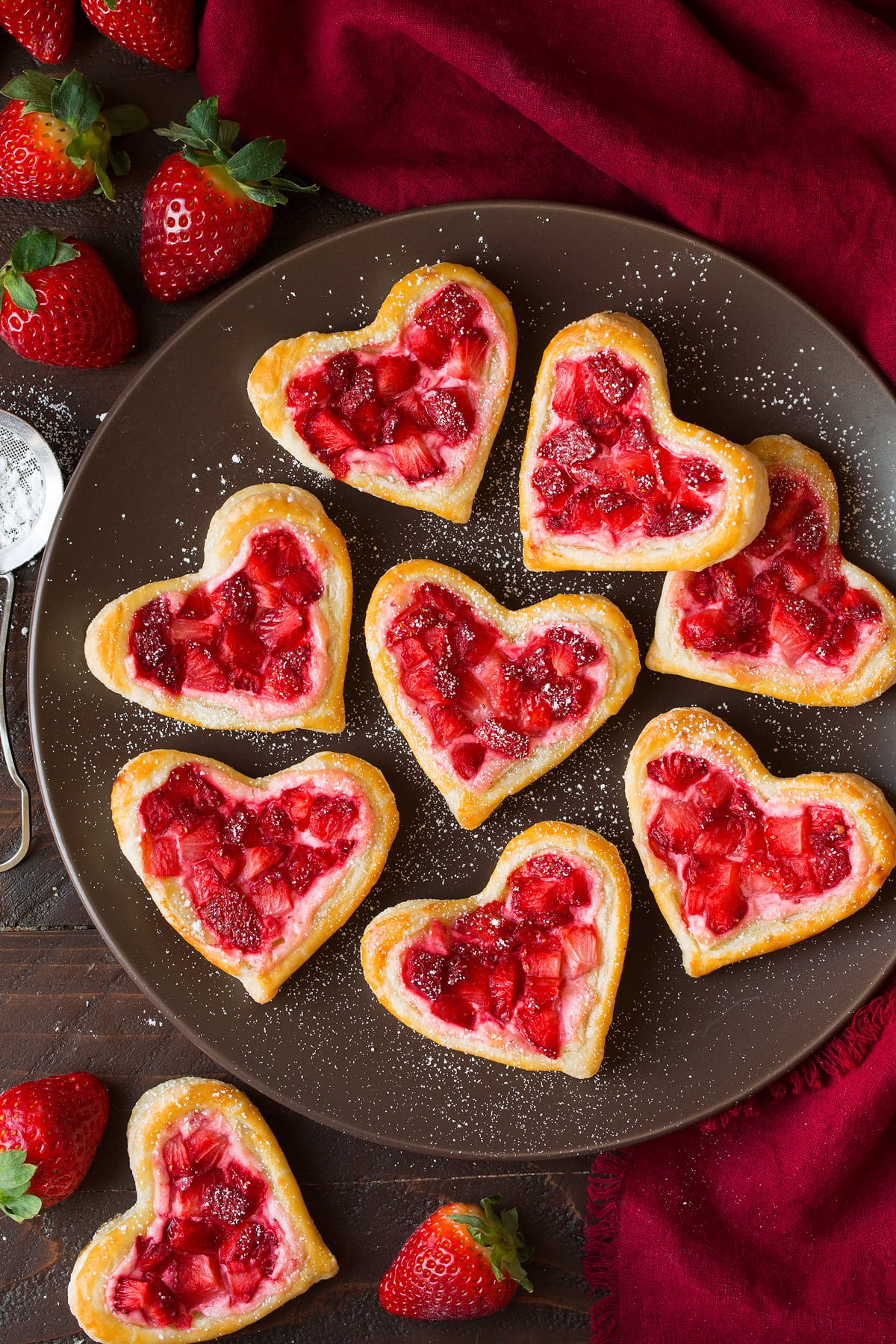 Breakfast Pastries cut into heart shapes, topped with sweetened cream cheese and strawberries.