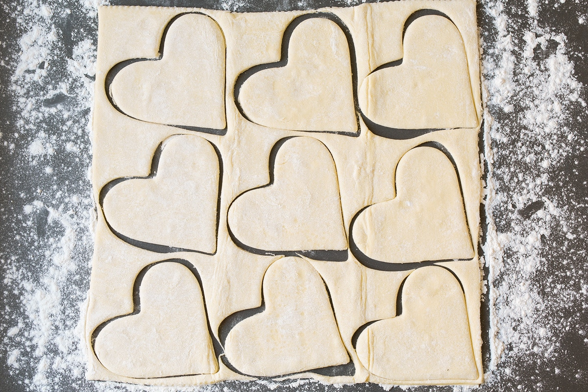 Cutting puff pastry into heart shapes.
