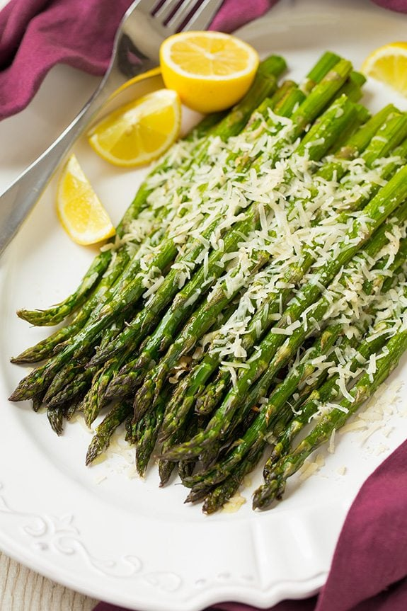 Roasted Parmesan Asparagus  on a white platter with lemon wedges