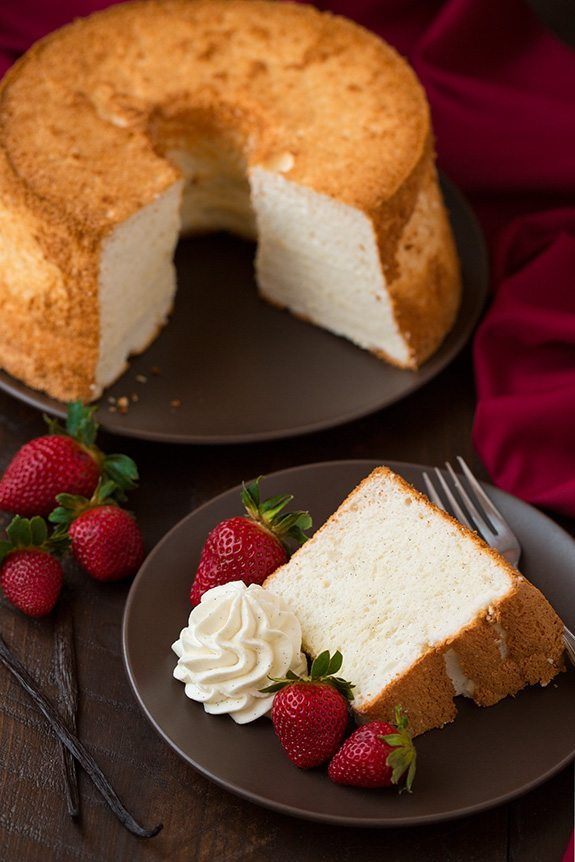 Vanilla Bean Angel Food Cake slice on plate in front of whole cake