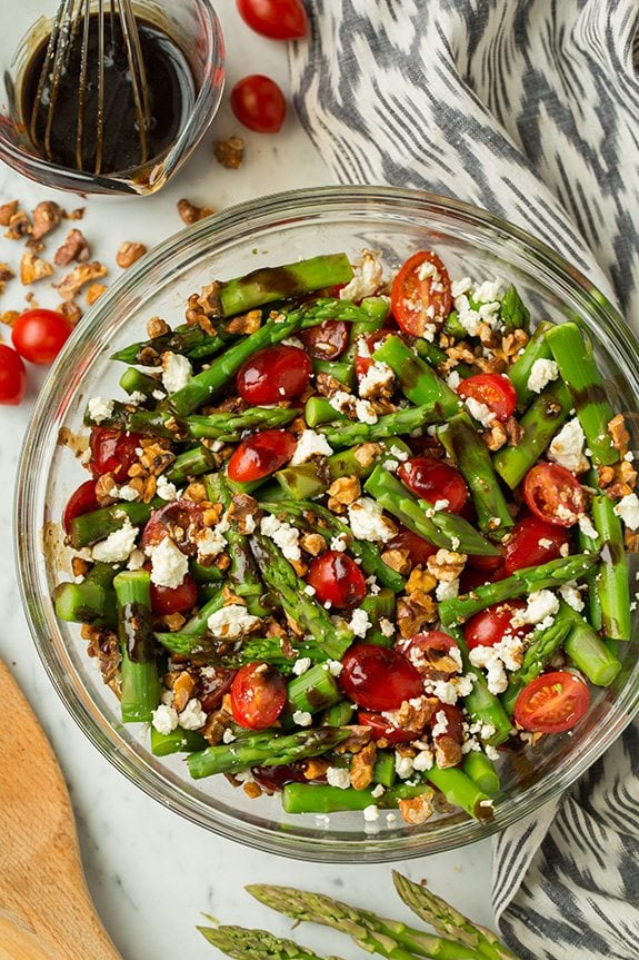 Asparagus, Tomato and Feta Salad in a glass bowl with Balsamic Vinaigrette at the side