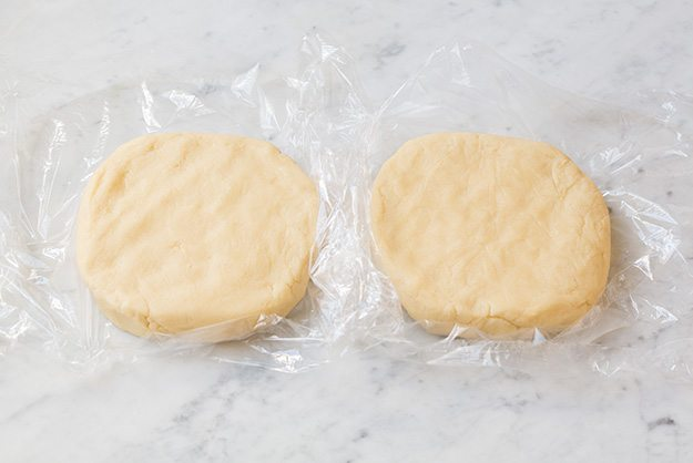 two discs of sugar cookie dough on plastic wrap