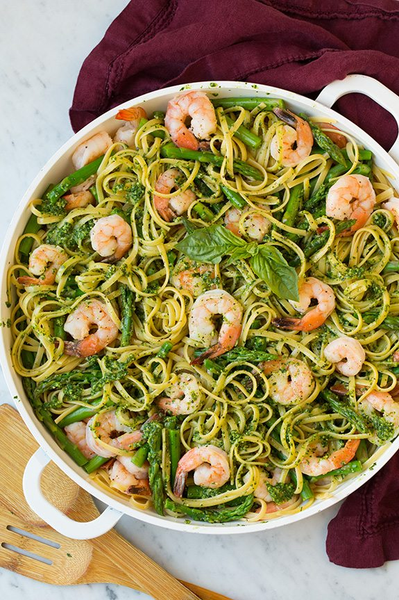 shrimp pesto pasta with asparagus in large white bowl