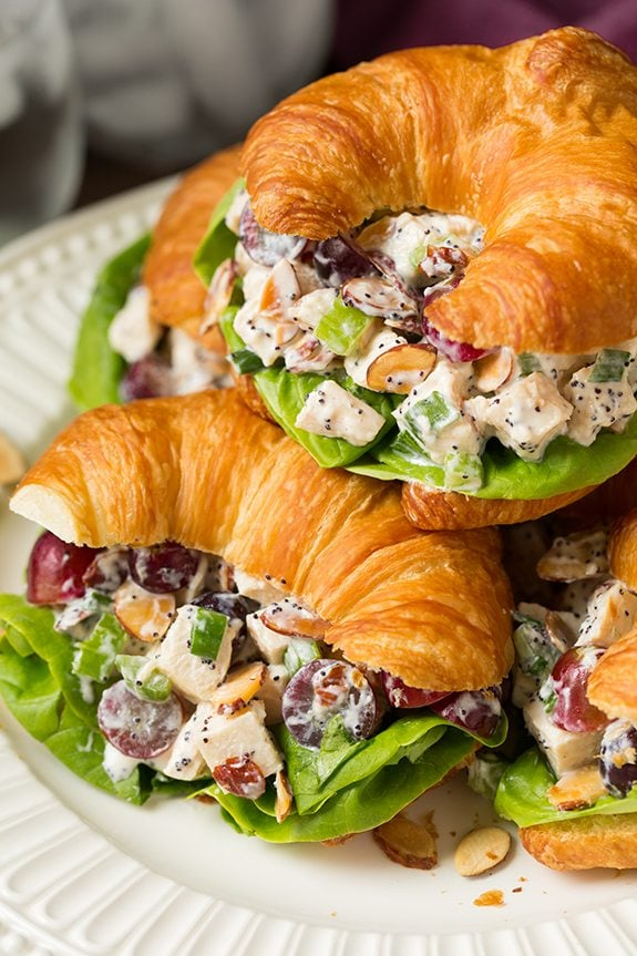 Three chicken salad sandwiches in croissants on a white serving plate. Chicken salad filling includes chicken breasts, grapes, celery, almonds and a creamy poppy seed dressing.