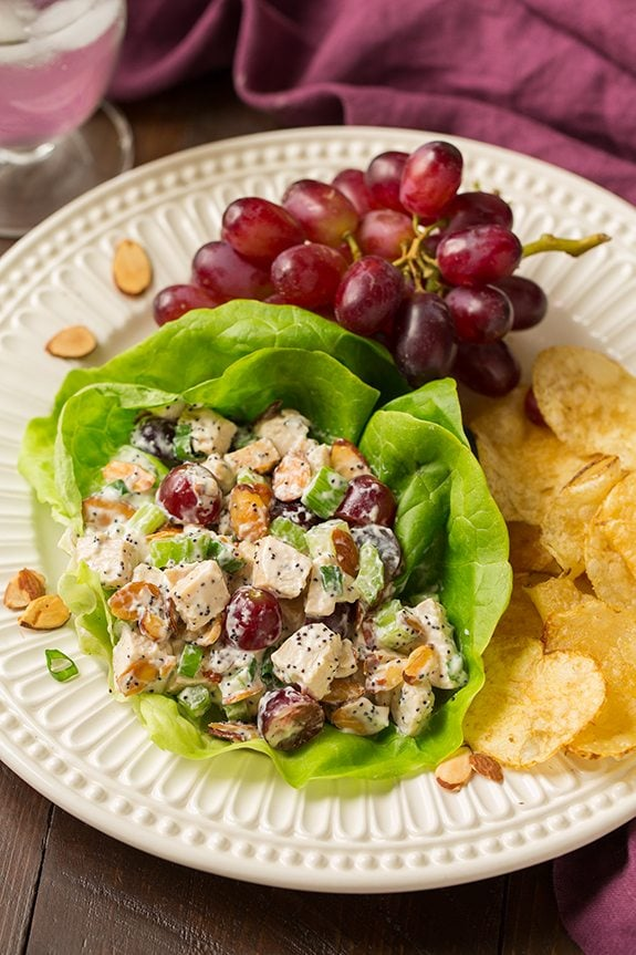 Chicken Salad served in a lettuce leaf on a white plate with a side of potato chips and grapes.