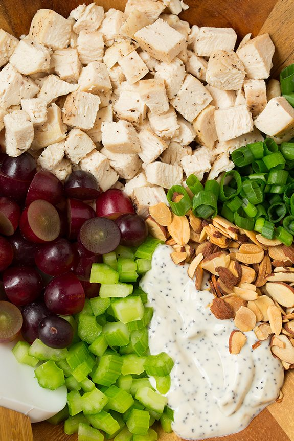 Chicken salad ingredients in a wooden bowl including chicken breasts, grapes, celery, almonds, green onions and poppy seed dressing. Ingredients shown in separate sections before mixing together.