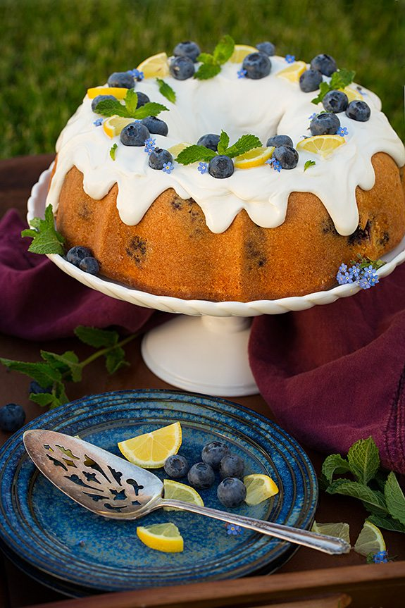 Lemon Blueberry Bundt Cake on cake stand behind blue plate