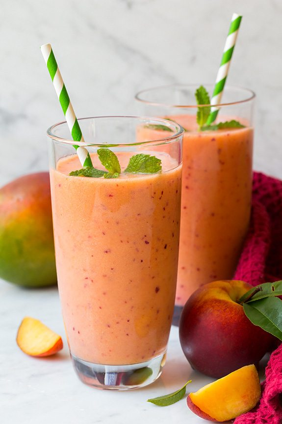 two glasses of mango strawberry peach smoothies with striped straws