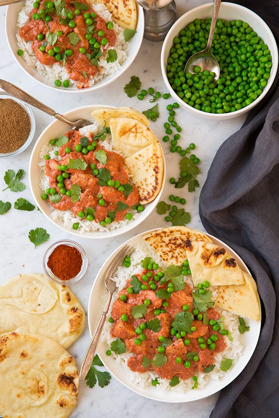 Easy Chicken Tikka Masala served with peas and naan over rice
