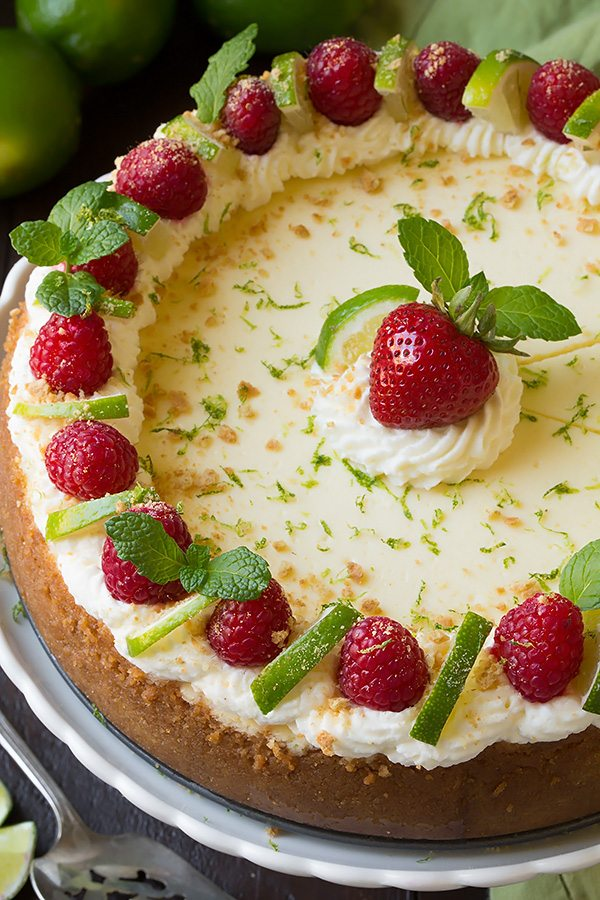 Whole Key Lime Cheesecake on a white serving plate. Cheesecake is garnished with whipped cream, raspberries, and limes along edges and a strawberry in center.