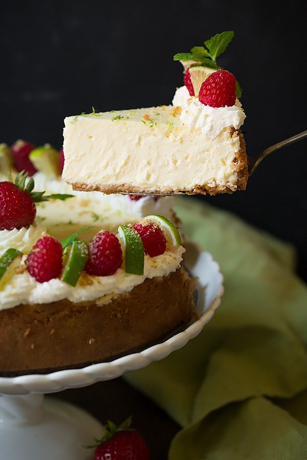 Lifting a slice of key lime cheesecake from the whole cake. It's garnished with whipped cream, raspberries, mint and graham crackers.