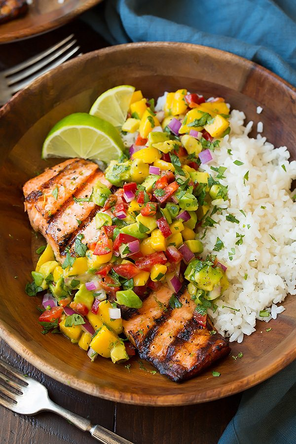 Grilled Lime Salmon in a wooden serving bowl topped with Mango-Avocado Salsa and served with a side of Coconut Rice