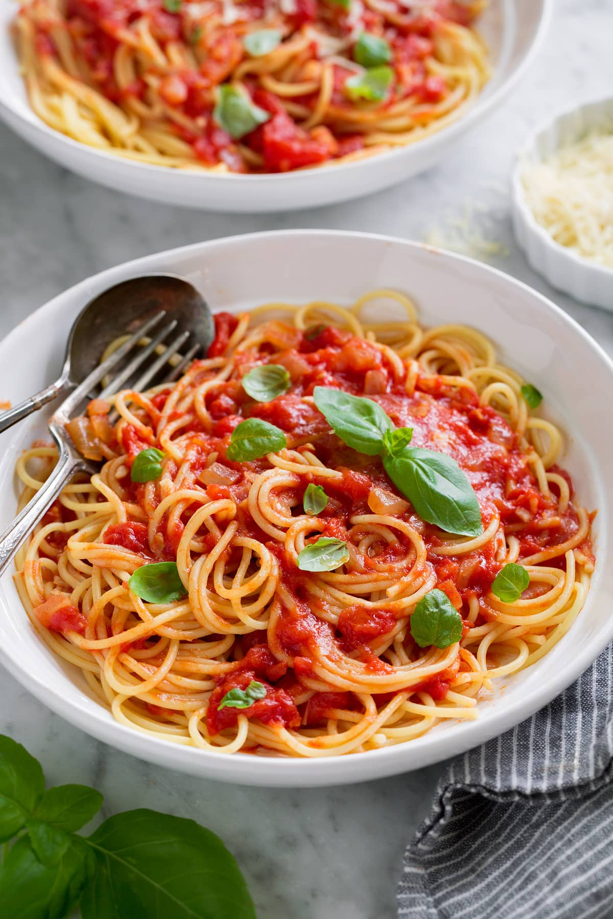 Marinara sauce served tossed with spaghetti, parmesan and fresh basil. Shown in a white pasta bowl.