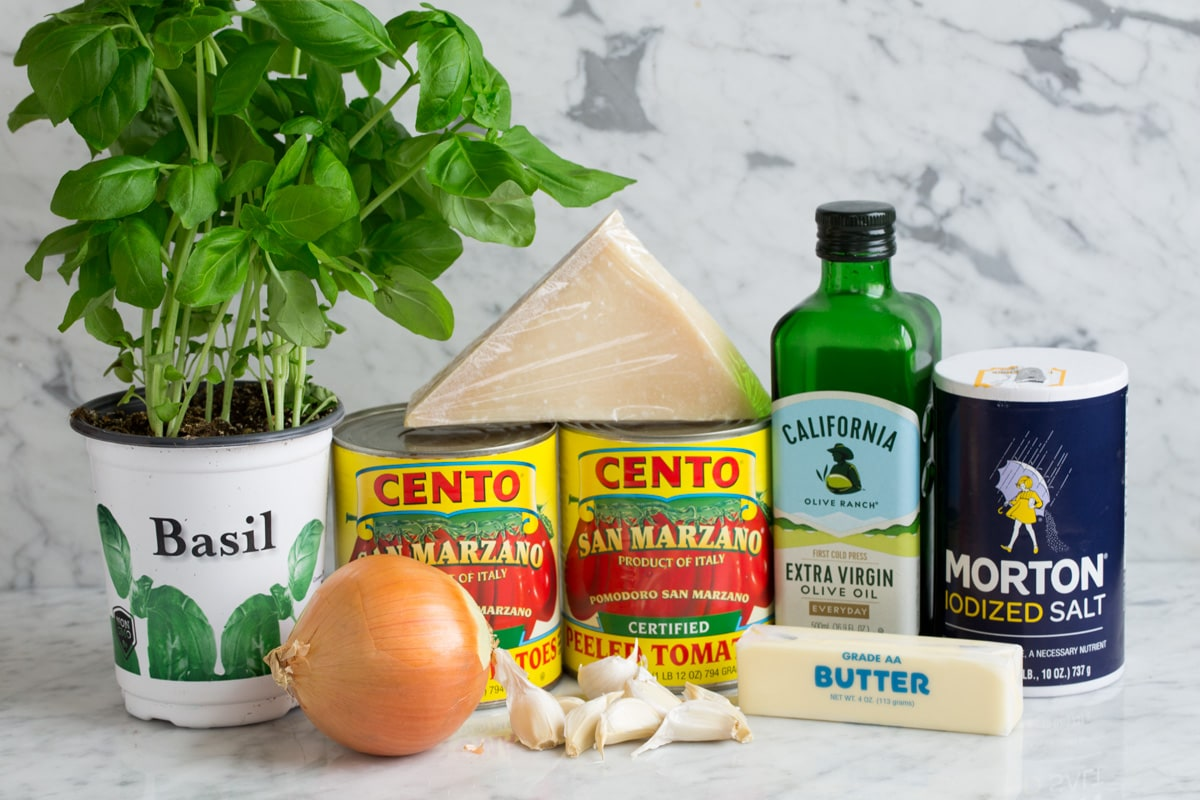 Ingredients needed to make marinara sauce shown here including canned San Marzano tomatoes, extra virgin olive oil, garlic, butter, parmesan, basil, onion, and salt.