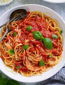 Marinara sauce tossed with spaghetti in a pasta bowl.