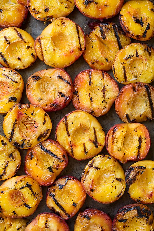 22 grilled peach halves on a baking sheet.