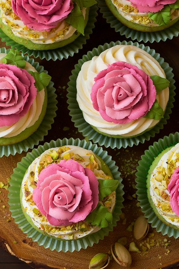 Pistachio cupcakes with pink piped buttercream roses on top.