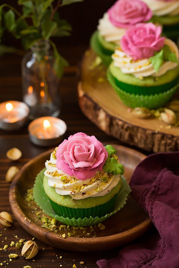 One pistachio cupcake on a wooden dessert plate. Cupcake is light green with a white buttercream frosting and it's topped with a pink piped rose.
