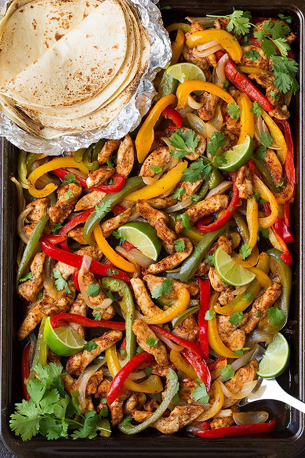 Chicken fajita mixture on a sheet pan with a side of tortillas. Fajita mixture includes seasoned chicken strips, bell peppers, onions and cilantro.
