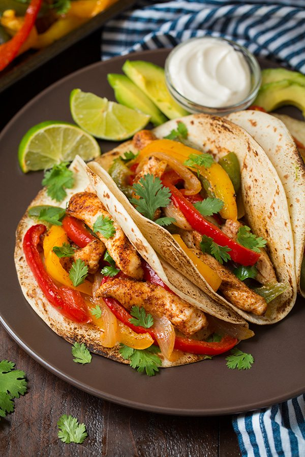 Chicken Fajitas wrapped in tortillas served with limes and sour cream on brown plate.