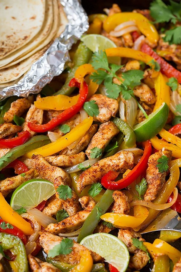 Close up image of chicken fajita mixture on a dark sheet pan.