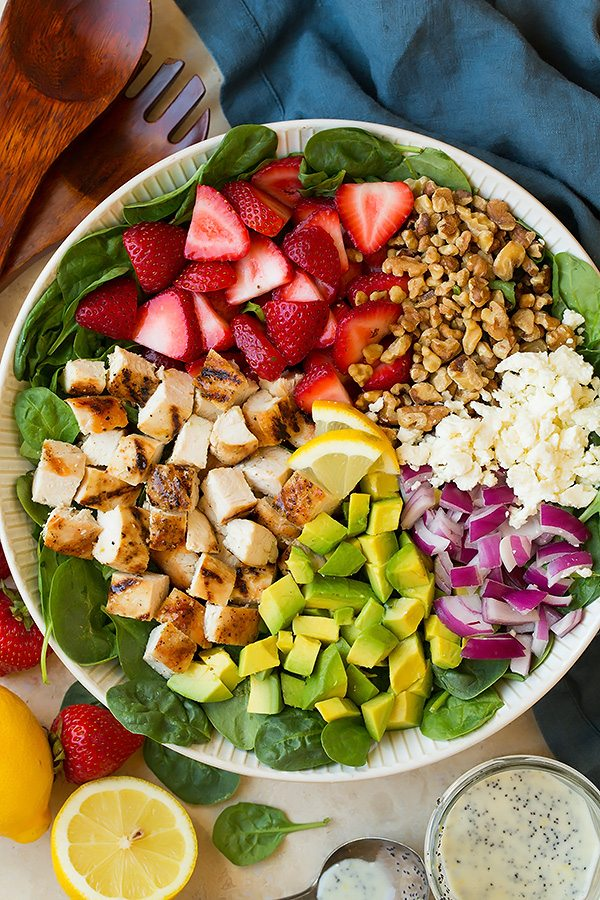strawberry spinach salad ingredients in a serving bowl before tossing.