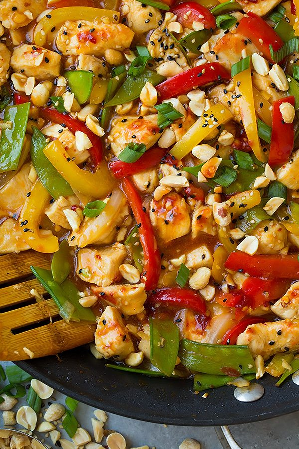 close up of Szechuan Chicken Stir-Fry topped with peanut and scallions