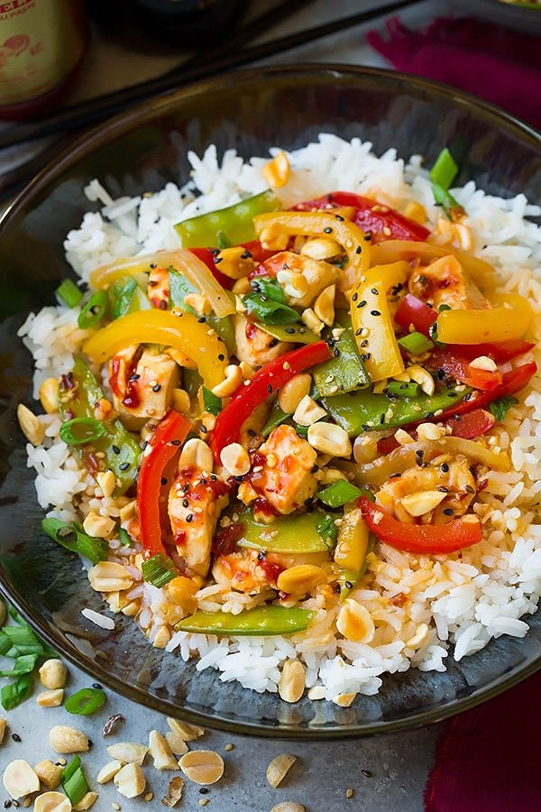 Szechuan Chicken Stir-Fry atop white rice in a dark bowl