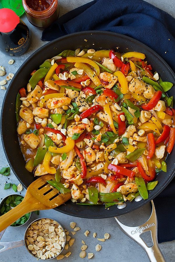 Szechuan Chicken Stir-Fry in metal skillet with wooden spatula
