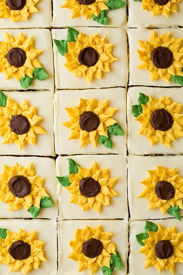 Overhead image of sliced zucchini cake in a baking dish. Each slice is topped with a piped buttercream sunflower.