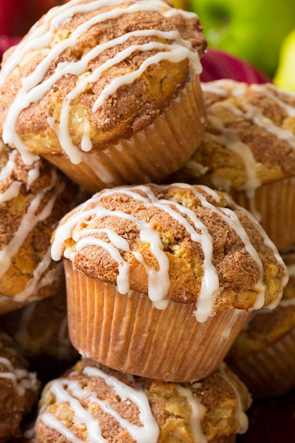 Close up image of two stacked apple muffins with crumble topping and vanilla glaze in parchment liners.