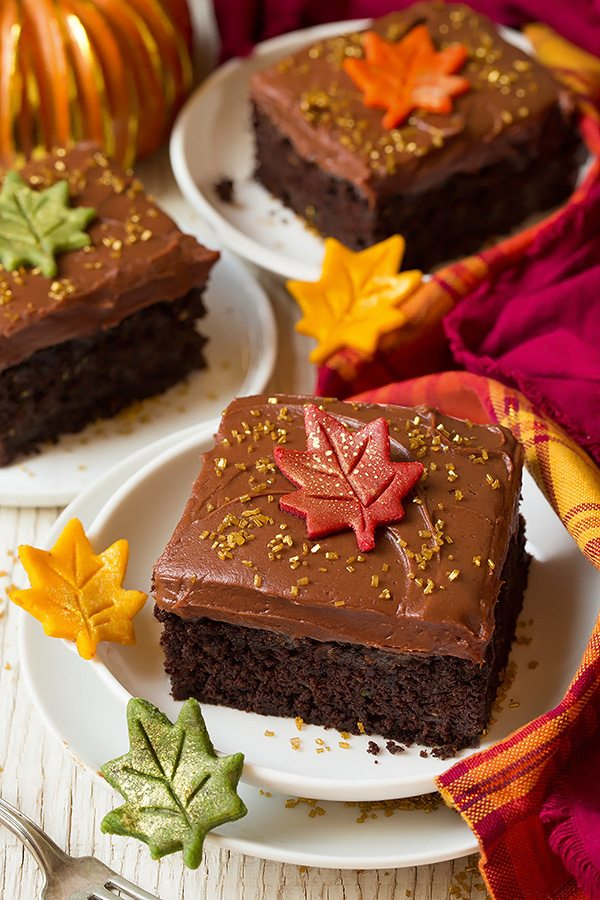 Three slices of chocolate zucchini cake on a individual dessert plates. They are decorated with chocolate cream cheese frosting, gold sprinkles and a autumn fondant leaf.