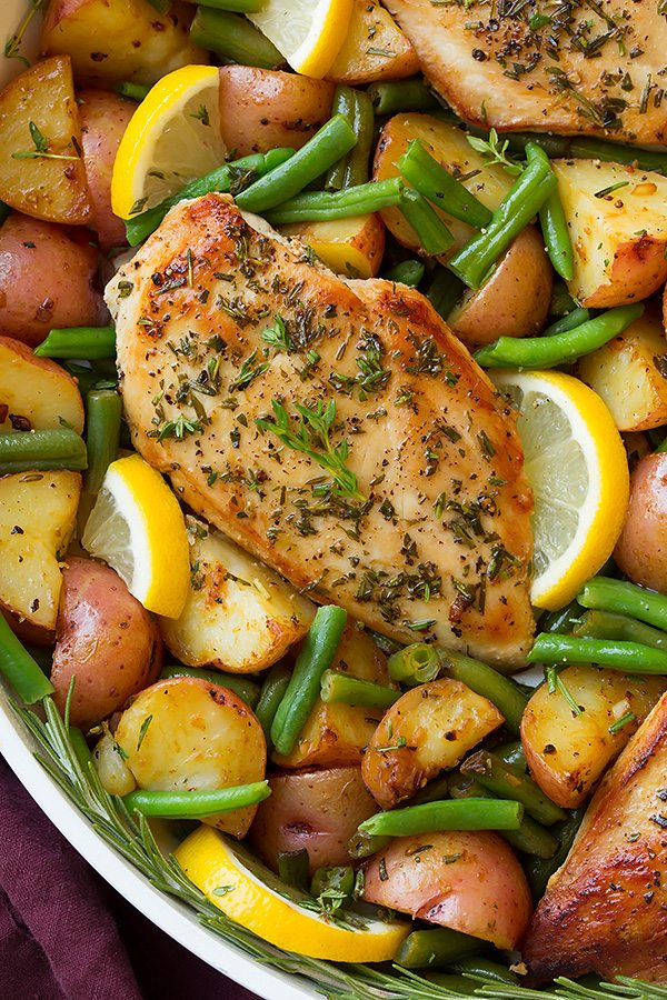 Garlic and herb seasoned chicken breasts in a skillet with green beans, potatoes and lemons.