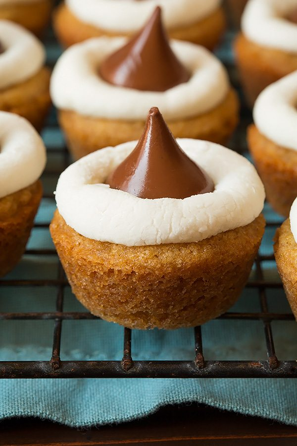Close up image of s'more cookie cup. Graham cracker cookie base with marshmallow halve in middle and a chocolate hershey's kiss on top.