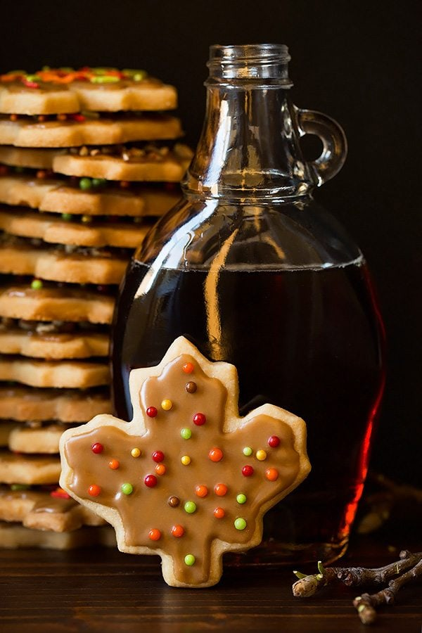 Shortbread cookie flavored with pale cut into leaf shape and set in front of a jar of maple syrup, in the background is a large stack of the shortbread cookies.