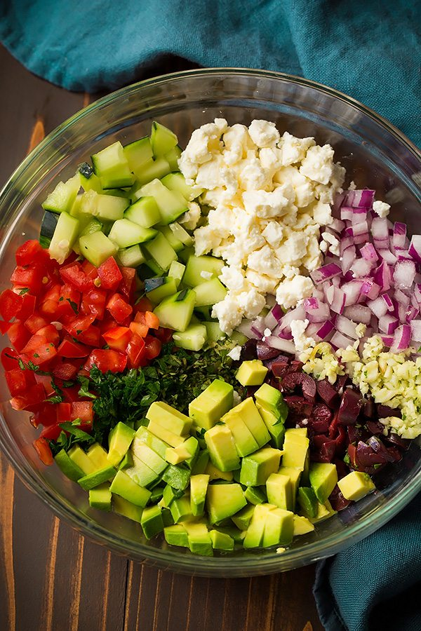 Greek salsa ingredients in a glass mixing bowl. Includes tomatoes, cucumbers, avocado, feta, red onion, garlic, olive and herbs.