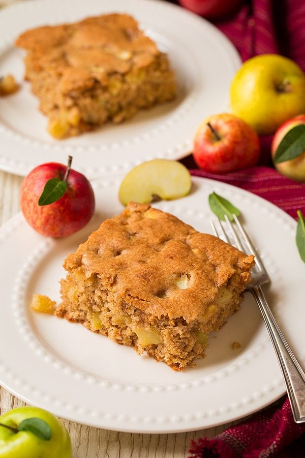 Two slices of apple cake on dessert plates.