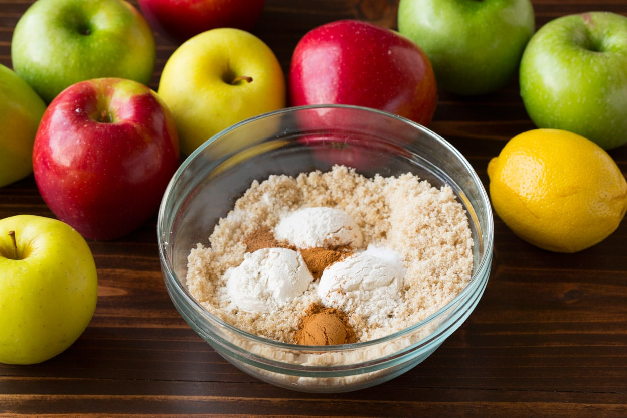 Mixing sugar and flour mixture in a small glass mixing bowl for apple pie filling.