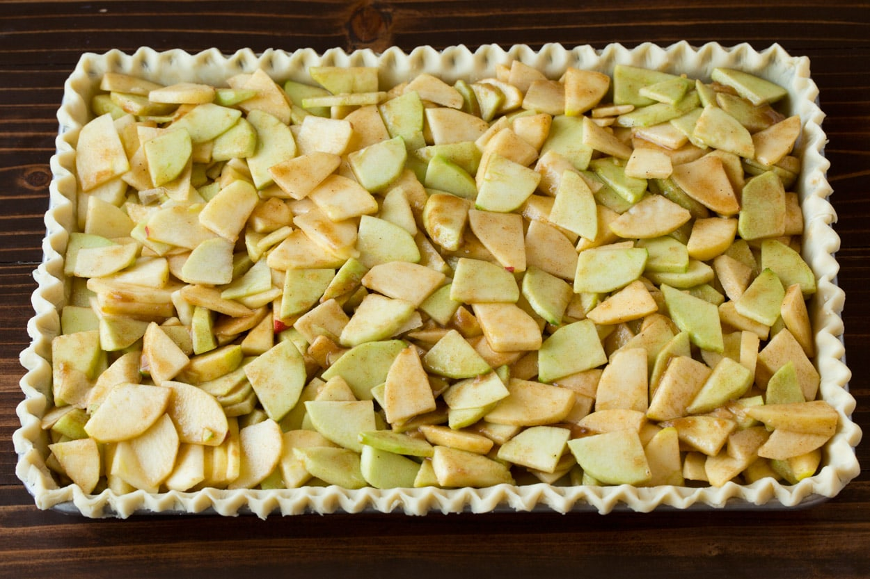 Apple filling added to crust layer for apple slab pie.