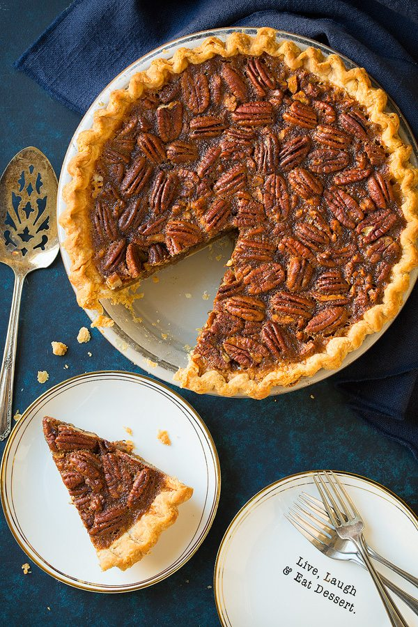 Overhead image of whole pecan pie in pie dish and a slice to one side. Pie is resting on a blue surface.