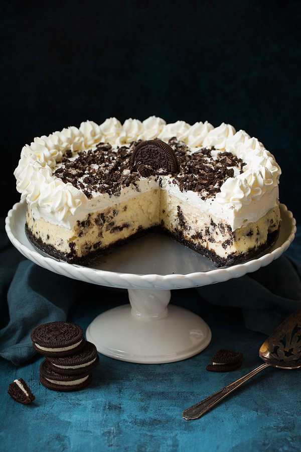 Oreo cheesecake on a cake stand with about 1/3 of the cake cut from one section to show inside of cheesecake.