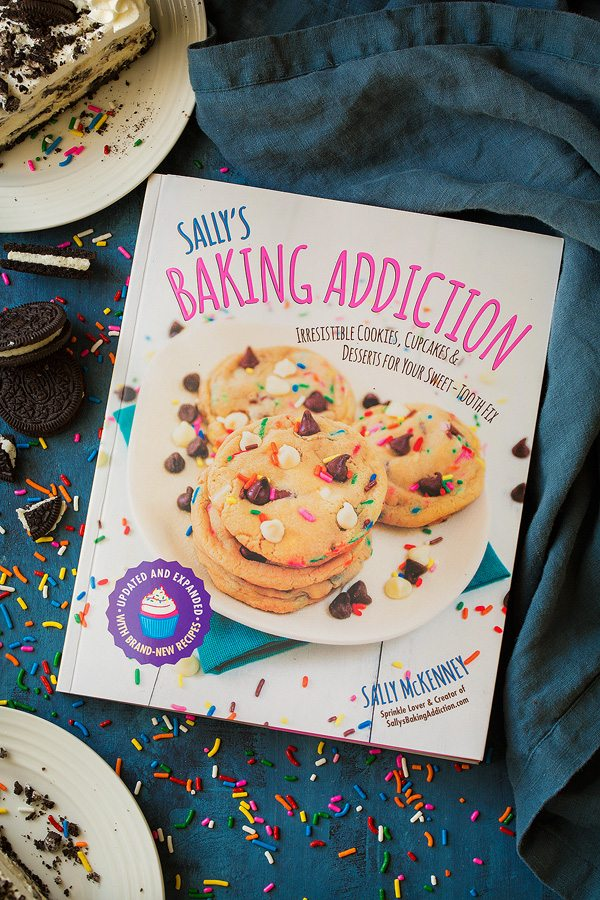 Sally's Baking Addiction Cookbook with recipe Oreo Cheesecake inside.