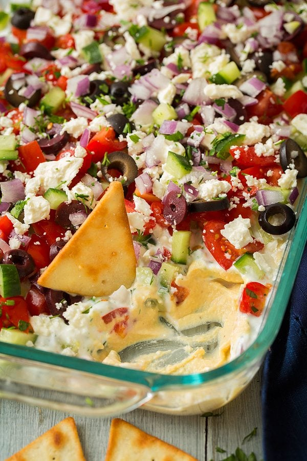 Greek Seven Layer Dip made with hummus, tomatoes, cucumbers, feta, olives and herbs.