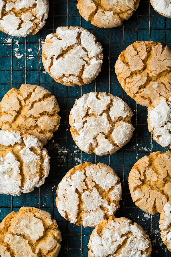 Peanut Butter Crinkle Cookies rolled in powdered sugar and baked. Tan peanut butter cookies are covered with powdered sugar and set on a black cooling rack over a blue cloth.