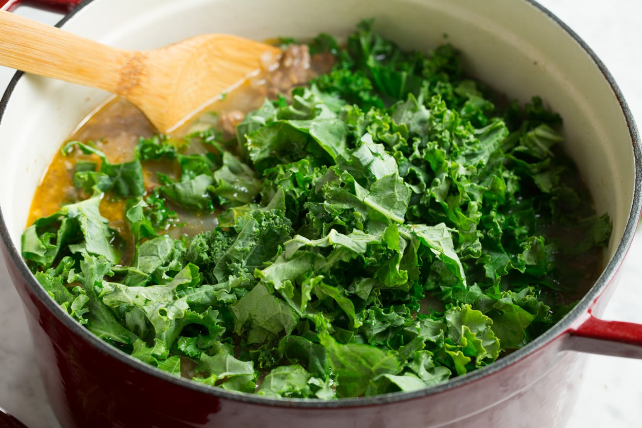 Adding kale to zuppa toscana soup in pot.