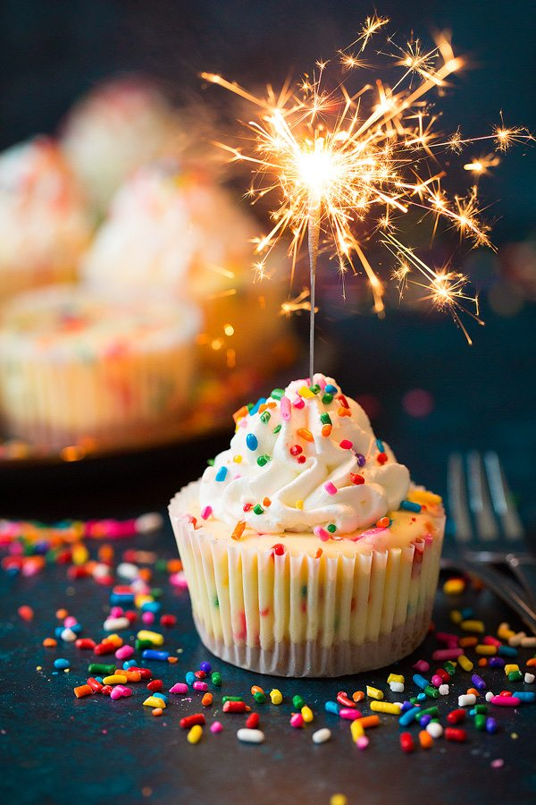 Mini cheesecake with sparkler lit resting in it.