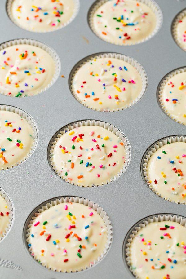 Cheesecake batter in 12 cupcake wells before baking.