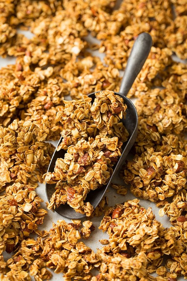 Close up image of honey almond granola in a metal scoop.